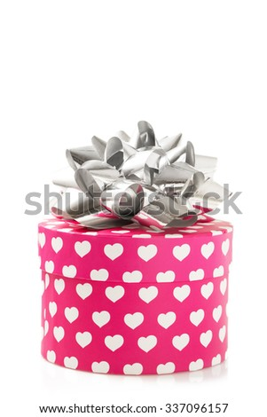 Pink gift box with white hearts and ribbon isolated on white background