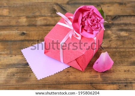 Pink gift with bow and flower on wooden table close-up - stock photo