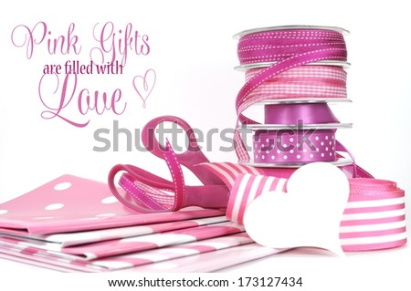 Pink Gifts are filled with Love, greeting with polka dot and plain ribbons, scissors, and wrapping paper for Valentines Day, Mothers Day, birthdays, wedding or Christmas gift wrapping. - stock photo