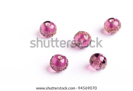 Pink glass beads with golden pattern closeup on white background - stock photo