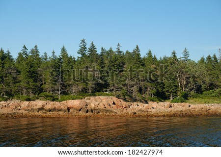 Pink Granite cliffs and green pine trees line a small safe cove and harbor - stock photo
