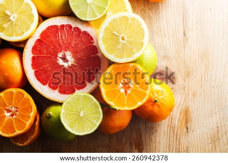Pink grapefruit and other citrus fruit against wooden background. Copy space. - stock photo