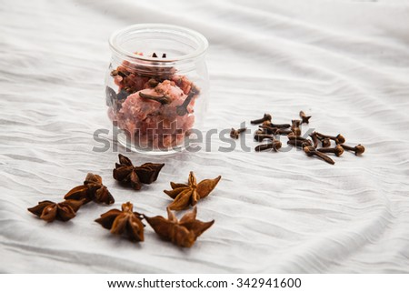 Pink handmade soap in transparent glass jar on a white tablecloth - stock photo