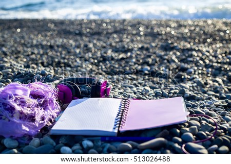 Pink headphones lying at paper notebook on sea beach. Closeup. Work and lifestyle concept. Freelancer. Music listening, Travel.