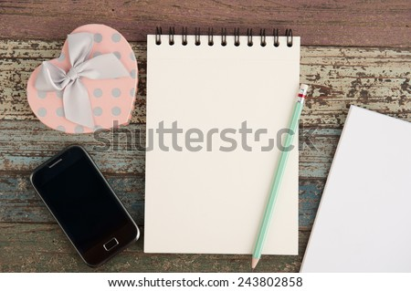 Pink Heart gift box phone and notebook on wood table background - stock photo