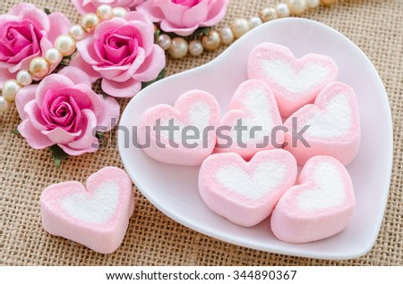 Pink heart marshmallows in white bowl with rose flower on sack background.