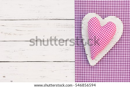 Pink heart on purple checkered fabric border on white wooden table background, top view, copy space.