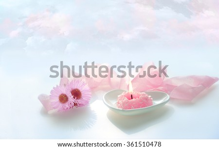 pink heart shaped burn candle with pink ribbon and flowers on blue sky background - stock photo