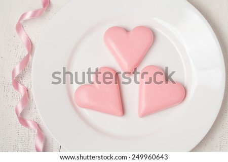 Pink heart-shaped jelly with ribbon on white dish for valentines day