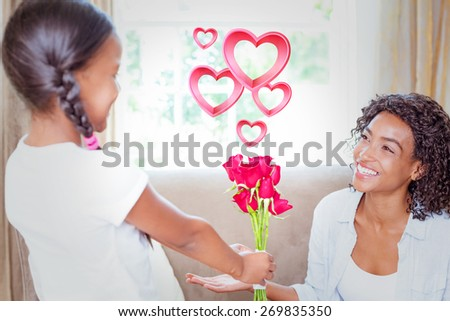 Pink hearts against pretty mother sitting on the couch with her daughter offering roses - stock photo