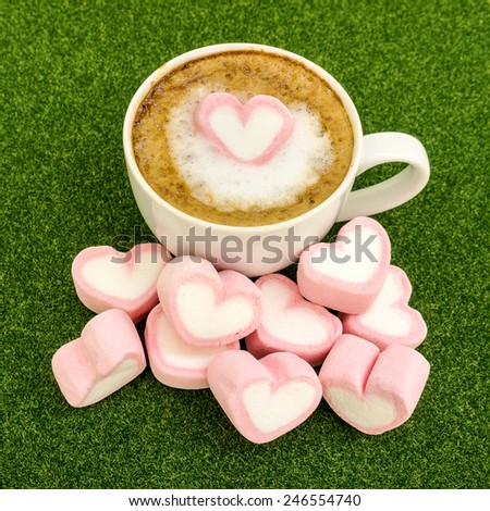 Pink hearts marshmallow groups on latte cofee for valentines green grass background. - stock photo