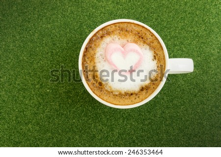 Pink hearts marshmallow on latte cofee for valentines green grass background - stock photo
