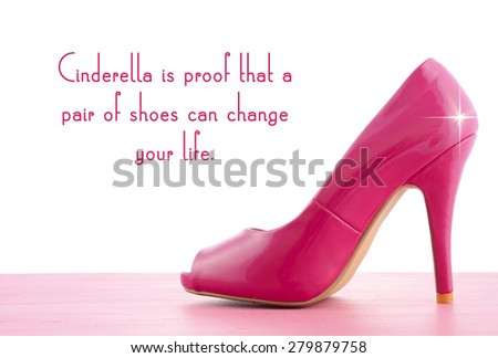 Pink high heel shoe on pink wood shabby chic table with Cinderella Is Proof quote. - stock photo