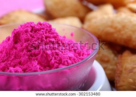 Pink Holi color with tradiional indian snacks gujiya - stock photo