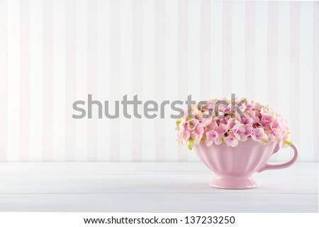 Pink hydrangea flowers in a shabby chic mug on vintage background with copy space - stock photo
