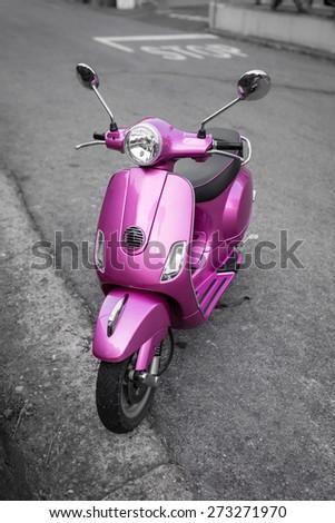 Pink italian scooter on the street - stock photo