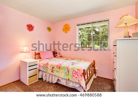 Pink kids bedroom with white furniture and carpet floor. Northwest, USA