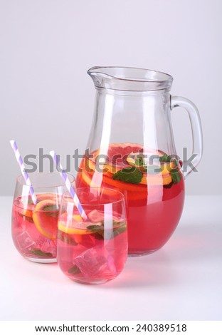 Pink lemonade in glasses and pitcher isolated on white - stock photo