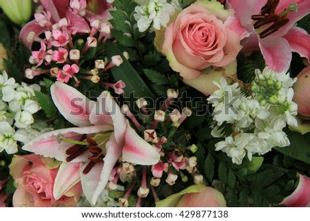 Pink lillies and roses in a pink and white wedding flower arrangement