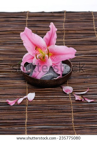 Pink lily with gray stones with petals in wooden bowl on mat - stock photo