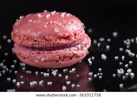 Pink macaroon cake an sugar over black background - stock photo