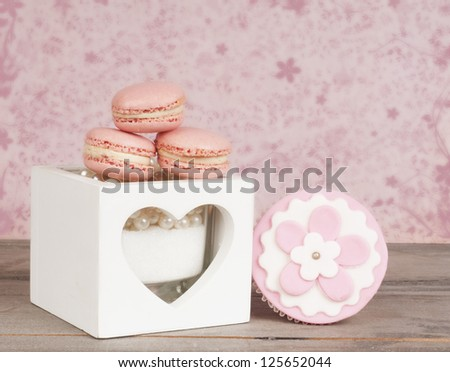 pink macaroons and flower decorated cupcake in romantic setting - stock photo