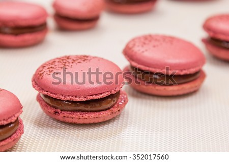 Pink macaroons with chocolate ganache on silicone mat. Cooking process ...