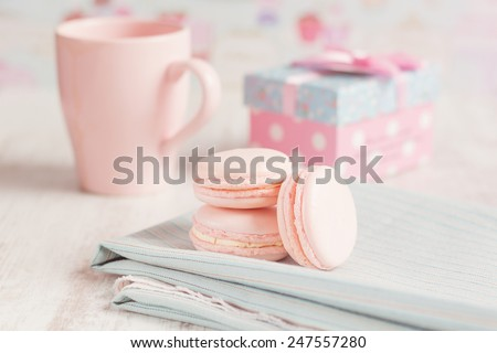 Pink macaroons with gift boxes and cup of coffee on background. Pastel colored - stock photo