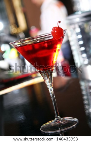 Pink martini cocktail served with cherry in a bar
