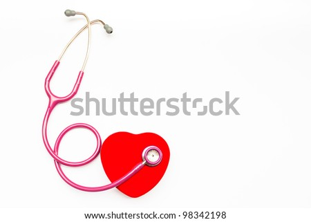Pink medical stethoscope and heart isolated on white