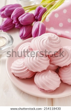 Pink meringues and tulip flowers - stock photo