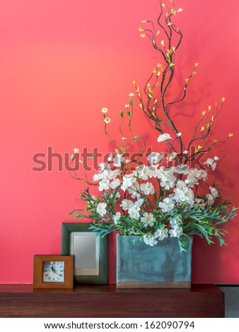 Pink modern interior wall with artificial flowers in ceramic vase - stock photo