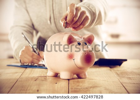 pink moneybox on table and hands and kitchen interior space  - stock photo