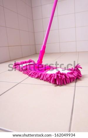 Pink mop cleaning light tile floor in bathroom - stock photo