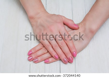 Pink nail art with white dots and lines on wooden background