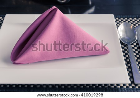 Pink napkin on white plate, table setting in retro filtered effect image - stock photo