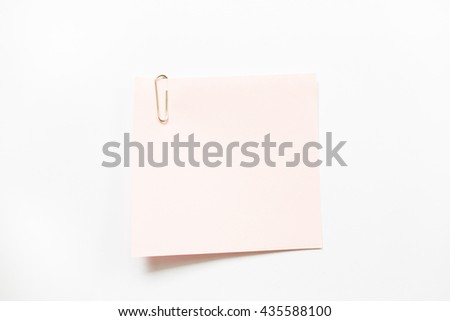 Pink note paper and paper clip isolate on white background.