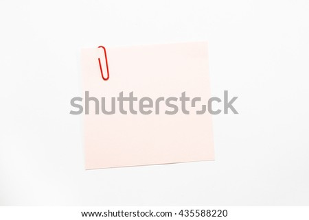 Pink note paper and red paper clip isolate on white background. - stock photo