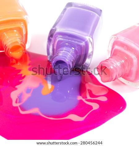 Pink, orange and purple nail polishes on the white background - stock photo