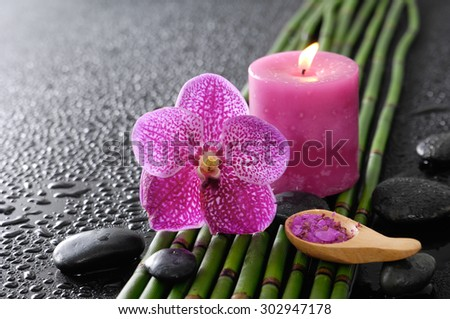 pink orchid and bamboo grove, petals in bowl, spoon on wet black background  - stock photo
