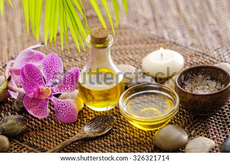Pink orchid and candle ,stone, palm ,salt in bowlon mat background