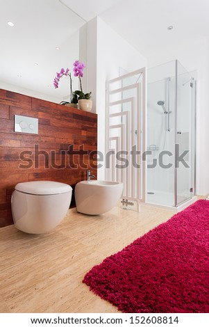 Pink orchid and cozy red carpet in bathroom - stock photo