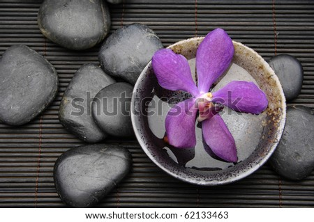 Pink orchid flower floating in wooden bowl with pebble on bamboo mat - stock photo