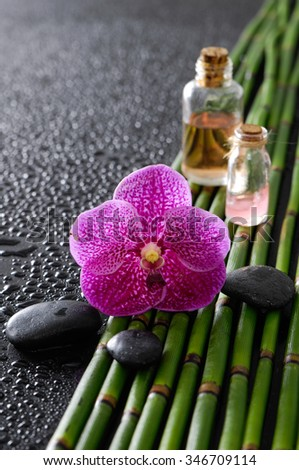 Pink orchid ,stones,oil,bamboo grove on wet black background   - stock photo