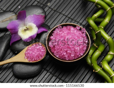 Pink orchid, with zen stone and sea salt in spoon on mat - stock photo