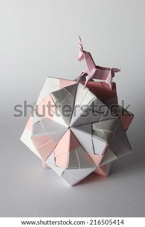 Pink origami unicorn riding colorful origami ball isolated on white - stock photo