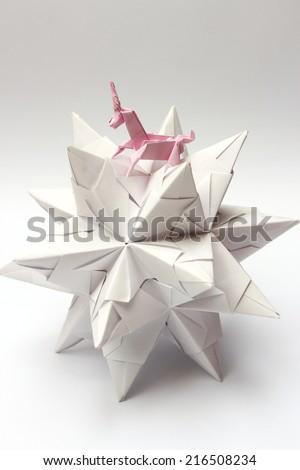 Pink origami unicorn riding modular origami star isolated on white - stock photo