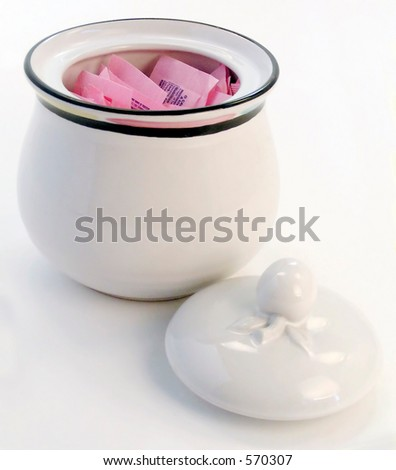 Pink packets of sugar substitute inside sugar bowl with lid. - stock photo