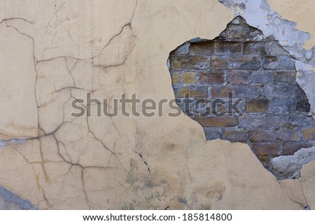 pink painted faded cracked wall with a brickwork - stock photo