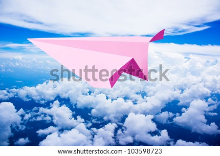 Pink paper plane flying against blue sky